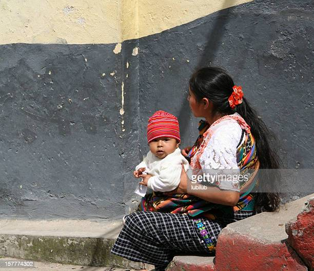 Mayan woman sitting by a wall with her little son