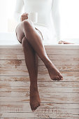Cropped image of gorgeous young African woman with beautiful legs sitting on the window sill and holding coffee cup