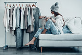 Thoughtful young woman in casual wear choosing the dress while sitting on the couch at home near her clothes hanging on the racks