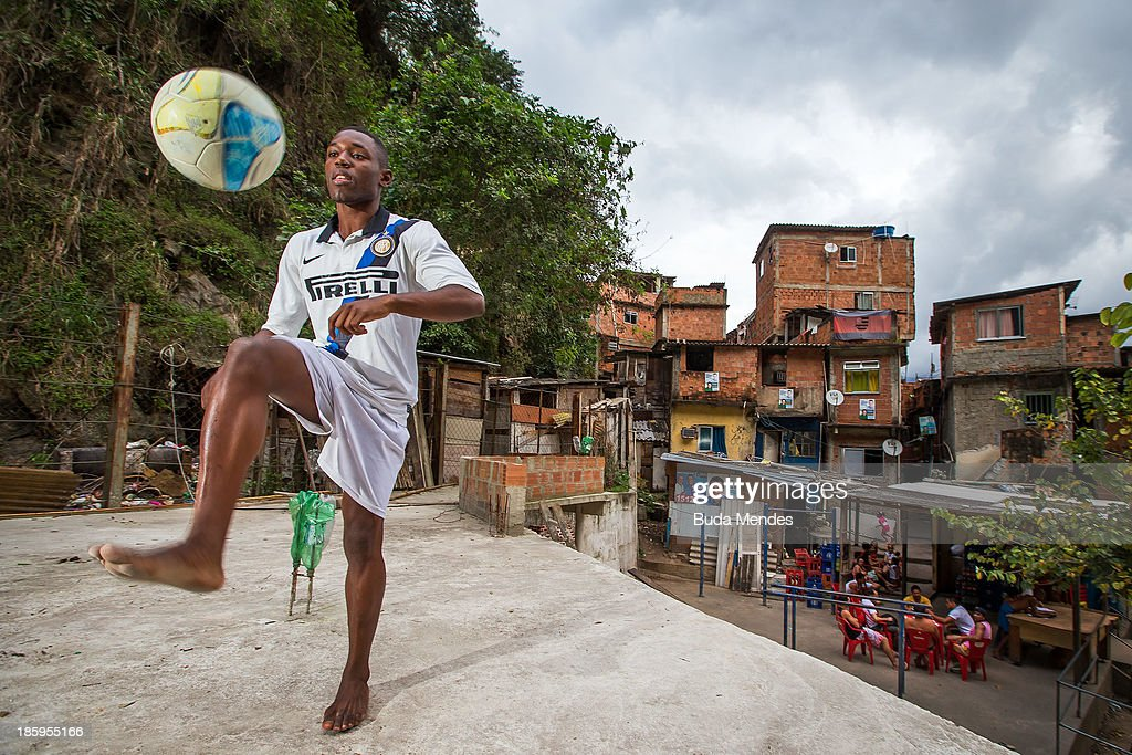 Maycon, athlete of Vila Nova Project, plays football on the rooftops in the Morro dos Macacos area on October 26, 2013 in Rio de Janeiro, Brazil. The Project Vila Nova was idealized by Alex Sandro and has so far run for 2 years, catering to children and young residents of the Morro dos Macacos area.