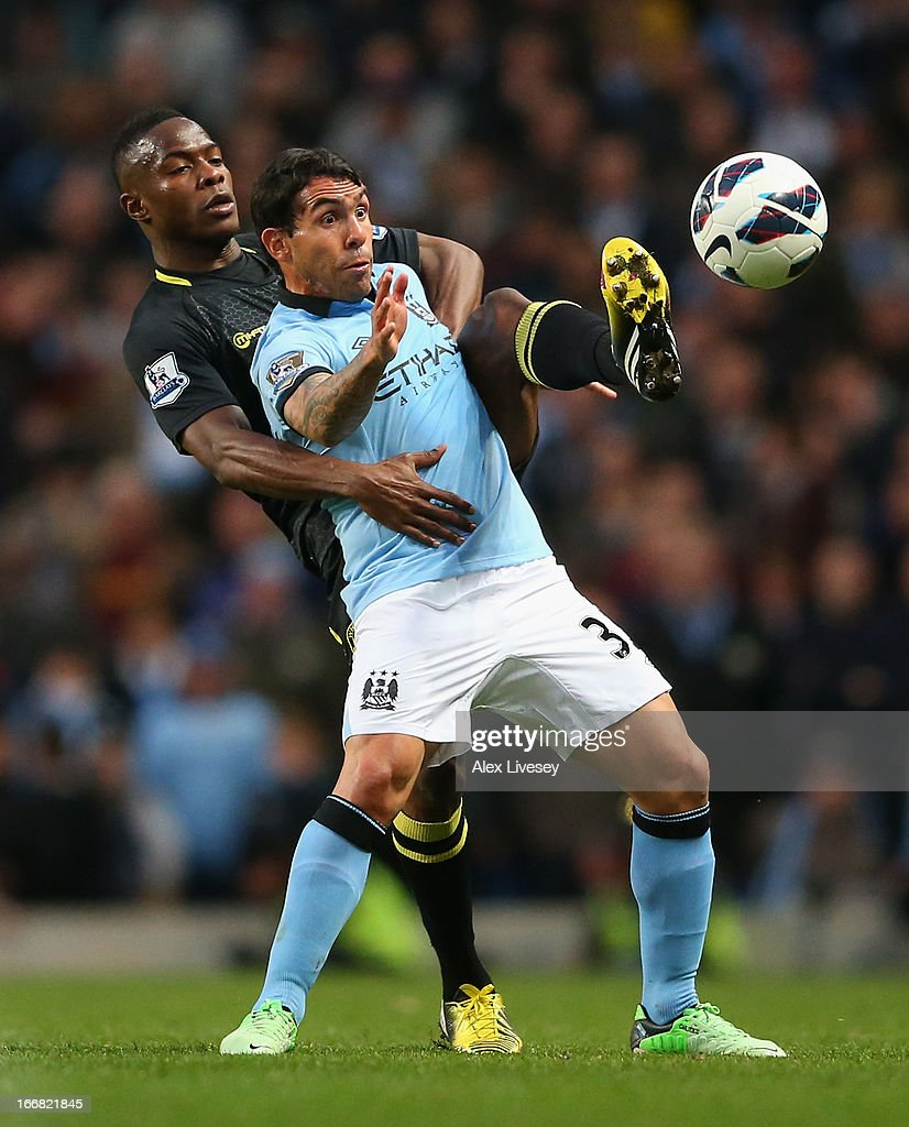 Maynor Figueroa of Wigan Athletic tangles with Carlos Tevez of Manchester City during the Barclays Premier League match between Manchester City and Wigan Athletic at the Etihad Stadium on April 17, 2013 in Manchester, England.