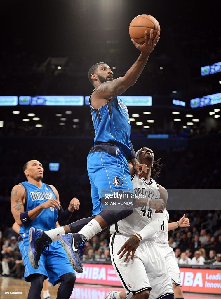 O.J. Mayo (C) of the Dallas Mavericks drives against Gerald Wallace (R) of the Brooklyn Nets at the Barclays Center March 1, 2013 in the Brooklyn borough of New York. AFP PHOTO/Stan HONDA