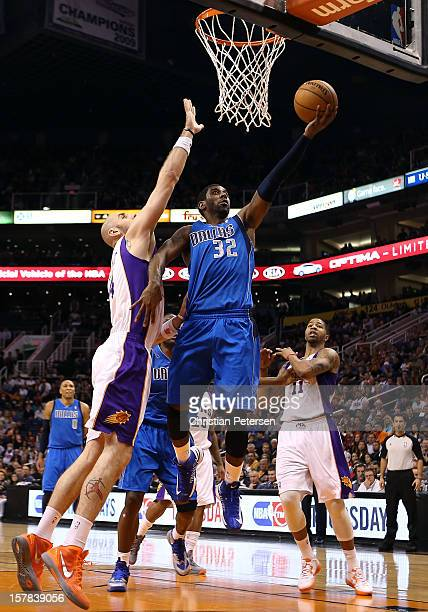 J Mayo of the Dallas Mavericks lays up a shot past Marcin Gortat of the Phoenix Suns during the NBA game at US Airways Center on December 6 2012 in...