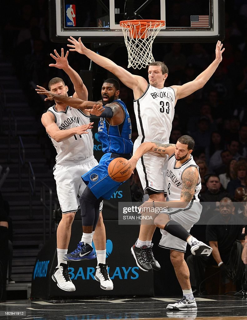 O.J. Mayo (C) of the Dallas Mavericks loses the ball against Brook Lopez (L), Mirza Teletovic (R) and Deron Williams (front) of the Brooklyn Nets at the Barclays Center March 1, 2013 in the Brooklyn borough of New York. The Mavericks won, 98-90. AFP PHOTO/Stan HONDA