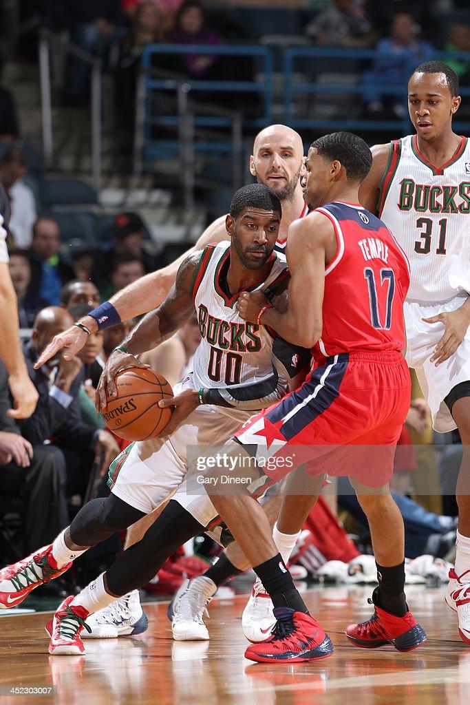Mayo of the Milwaukee Bucks drives against Garrett Temple of the Washington Wizards on November 27 2013 at the BMO Harris Bradley Center in Milwaukee...
