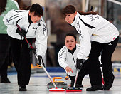 Mayo Yamura of Japan has her stone swept by teammates Kotomi Ishizaki and Mari Motohashi in the Women's Curling during day three of the Winter Games...