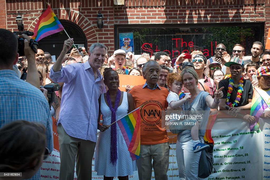 Mayor Bill de Blasio and First Lady Chirlane McCray with Rev. Al Sharpton and Cynthia Nixon with her son Max, stand for a photograph outside the Stonewall Inn during the 46th annual Gay Pride march June 26, 2016 in New York. New York kicked off June 26 what organizers hope will be the city's largest ever Gay Pride march, honoring the 49 people killed in the Orlando nightclub massacre and celebrate tolerance. / AFP / the 46th / Bryan R. Smith
