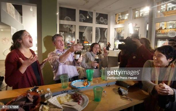 Mayor Ethan Strimling pops the cork off a bottle of champagne while celebrating with supporters of the Protect Our Neighborhood Schools campaign...