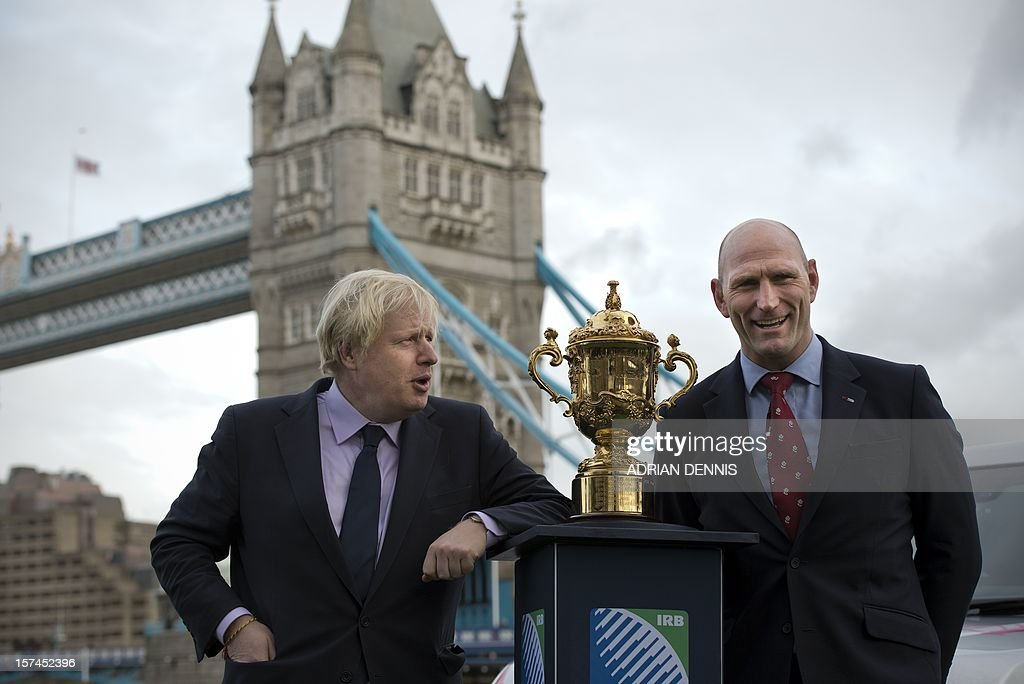 Mayor for London Boris Johnson (L) and former England rugby player Lawrence Dallaglio pose for a photograph beside The Webb Ellis Cup, close to Tower Bridge ahead of the Rugby World Cup draw in London on December 3, 2012. Teams in the top three bands are to be drawn for the England 2015 tournament. There will be four pools of five teams to compete at the Rugby World Cup 2015. Band 1 consists of: New Zealand, South Africa, Australia and France. Band 2 consists of: England, Ireland, Samoa and Argentina. Band 3 consists of Wales, Italy, Tonga and Scotland. The final two positions in each pool will be allocated to the eight qualifying places which are still available. AFP PHOTO / ADRIAN DENNIS