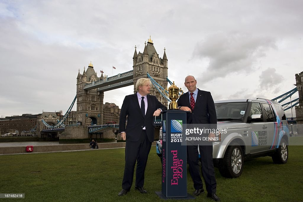 Mayor for London Boris Johnson (L) and former England rugby player Lawrence Dallaglio pose for a photograph beside The Webb Ellis Cup, close to Tower Bridge ahead of the Rugby World Cup draw in London on December 3, 2012. Teams in the top three bands are to be drawn for the England 2015 tournament. There will be four pools of five teams to compete at the Rugby World Cup 2015. Band 1 consists of: New Zealand, South Africa, Australia and France. Band 2 consists of: England, Ireland, Samoa and Argentina. Band 3 consists of Wales, Italy, Tonga and Scotland. The final two positions in each pool will be allocated to the eight qualifying places which are still available.