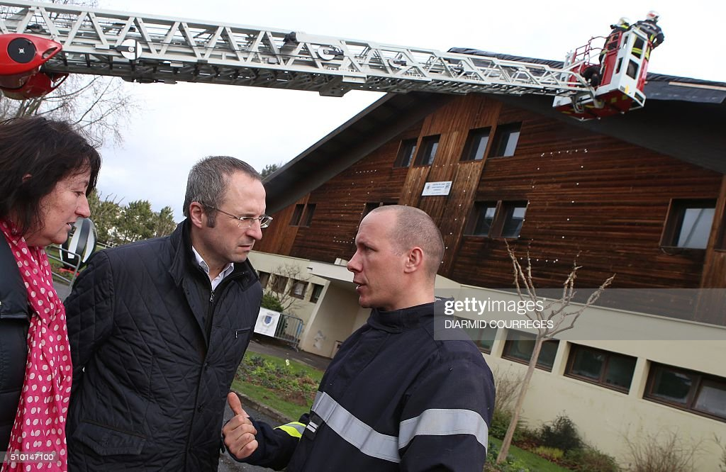 Mayor Frederic Soulier (2nd L) talks with a firefighter as other firefighters assess damages on the roof of the municipal tennis court in Brive-la-Gaillarde, southwestern France, on February 14, 2016 after a small tornado hit the town. About 15,000 homes were still without power Fabruary 14, including 3,000 in the Landes department and 3,000 in the Pyrenees-Atlantiques, after a storm raged through the southwest overnight. / AFP / DIARMID COURREGES