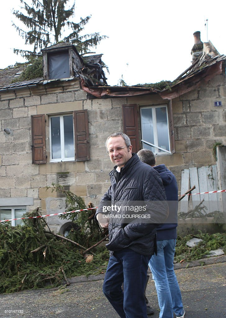 Mayor Frederic Soulier walks past house that was damaged by an uprooted tree as he assesses damages through the town of Brive-la-Gaillarde, southwestern France, on February 14, 2016 after a small tornado hit the town. About 15,000 homes were still without power Fabruary 14, including 3,000 in the Landes department and 3,000 in the Pyrenees-Atlantiques, after a storm raged through the southwest overnight. / AFP / DIARMID COURREGES
