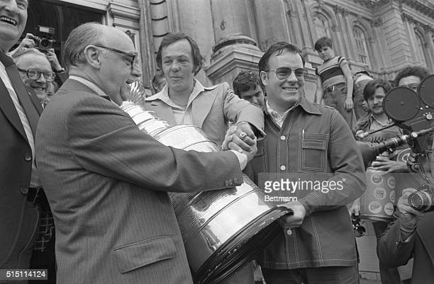 Mayor Jean Drapeau congratulates Montreal Canadiens' team caption Yvan Cournoyer and coach Scotty Bowman as they display the Stanley Cup at City Hall...