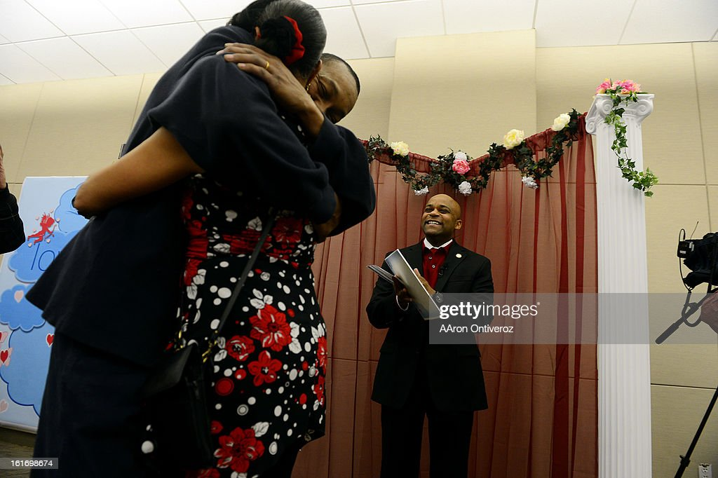 Mayor Michael Hancock claps after marrying Delani Eugene Simmons and Lavette Michelle Noel during a Valentine's Day marriage celebration at the Denver Clerk and Recorder's office. Couples applying for marriage licenses received gift bags containing gift certificates to local restaurants among other treats to celebrate their union.