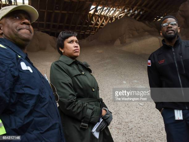 Mayor Muriel Bowser center inspects a pile of rocksalt with Chris Shorter Director of the DC Department of Public Works right and Jerry Brown a...