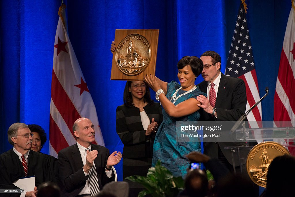 Mayor Muriel Bowser hold the Seal of the District as former Mayor Vincent Gray and councilman Phil Mendelson look on at the inaugural ceremony in Washington, DC on January 2, 2015. Bowser and other councilmembers were sworn into office today.