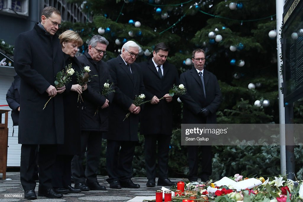 Mayor of Berlin, Michael Muller, German Chancellor Angela Merkel, German Interior Minister Thomas de Maiziere and Interior Senator, Andreas Geisel lay flowers near where yesterday a lorry ploughed through a Christmas market on December 20, 2016 in Berlin, Germany. So far 12 people are confirmed dead and 45 injured. Authorities have confirmed they believe the incident was an attack and have arrested a Pakistani man who they believe was the driver of the truck and who had fled immediately after the attack. Among the dead are a Polish man who was found on the passenger seat of the truck. Police are investigating the possibility that the truck, which belongs to a Polish trucking company, was stolen yesterday morning.