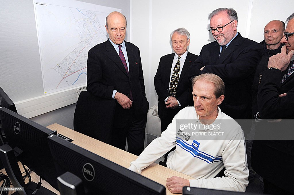 Mayor of Bordeaux and candidate for Les Republicains right-wing party primary Alain Juppe (L) watches a presentation of police video-surveillance system in Meylan, eastern france, with Mayor of Meylan Damien Guiguet (R) as part of a trip in Grenoble on February 10, 2016. / AFP / JEAN-PIERRE CLATOT
