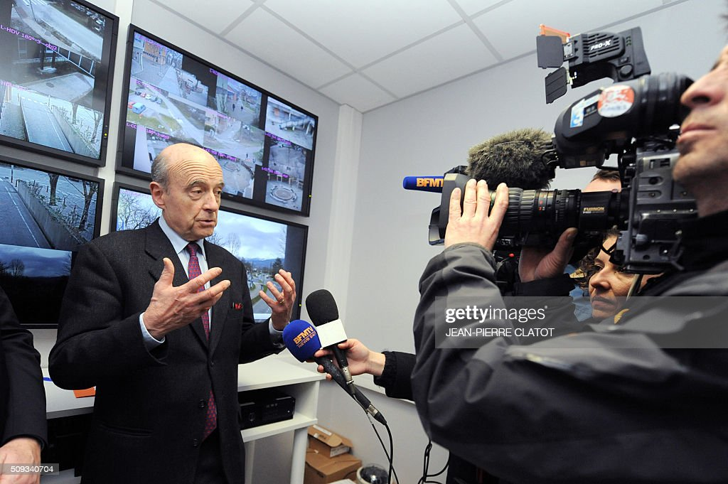 Mayor of Bordeaux and candidate for Les Republicains right-wing party primary Alain Juppe gestures as he answers questions to journalists as part of a presentation of police video-surveillance system in Meylan, eastern france on February 10, 2016. / AFP / JEAN-PIERRE CLATOT