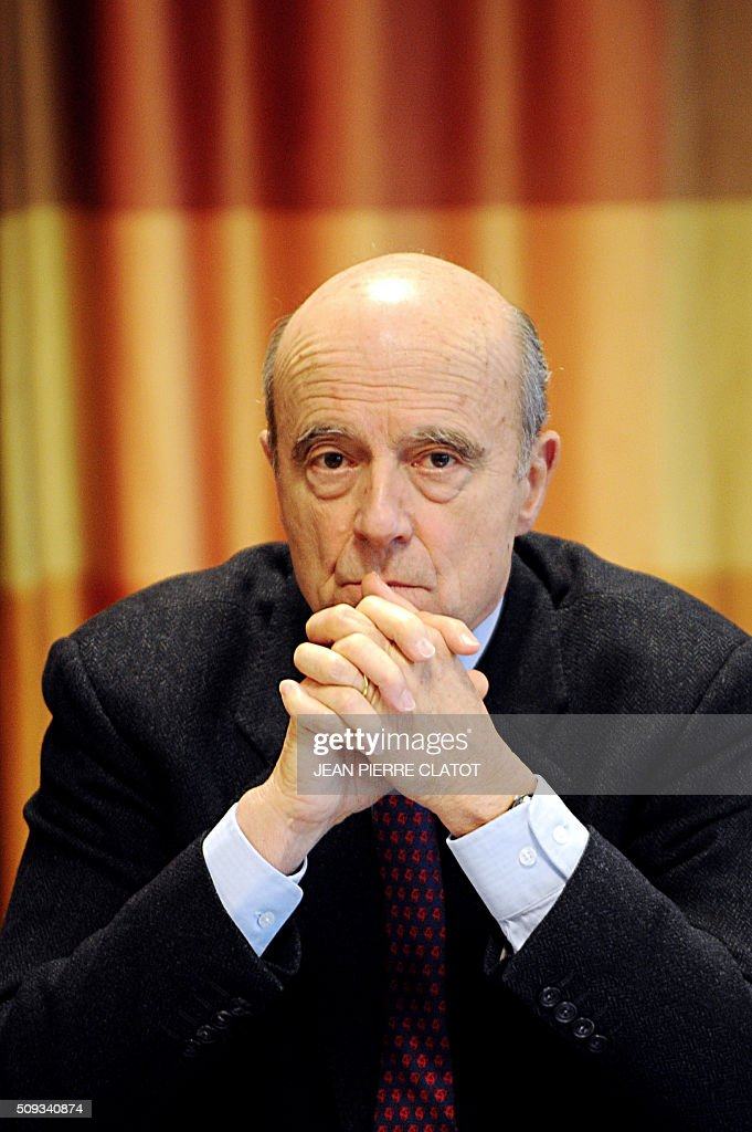 Mayor of Bordeaux and candidate for Les Republicains right-wing party primary Alain Juppe (C) looks on during a meeting with stakeholders about security in Meylan, eastern france on February 10, 2016. / AFP / JEAN PIERRE CLATOT