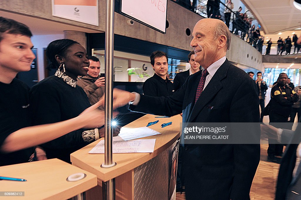 Mayor of Bordeaux and candidate for Les Republicains right-wing party primary Alain Juppe shakes hands with a student of a management school and institute of political studies at the chamber of commerce and industry in Grenoble, eastern France, on February 10, 2016. / AFP / JEAN PIERRE CLATOT