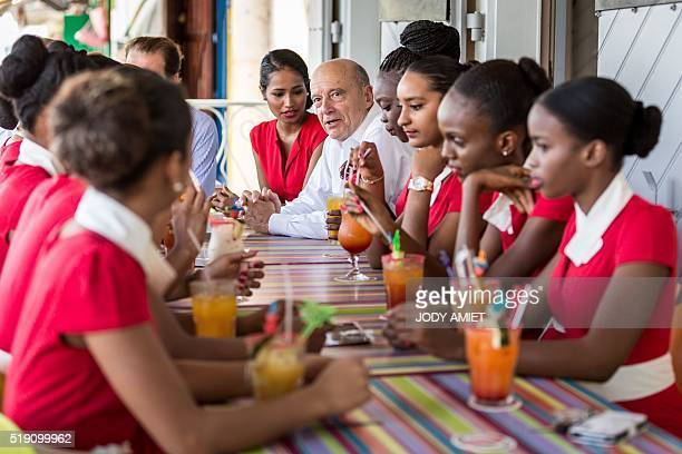Mayor of Bordeaux and candidate for Les Republicains rightwing party primary Alain Juppe talks with Guianese youth at the cafe terrace of the Bar des...