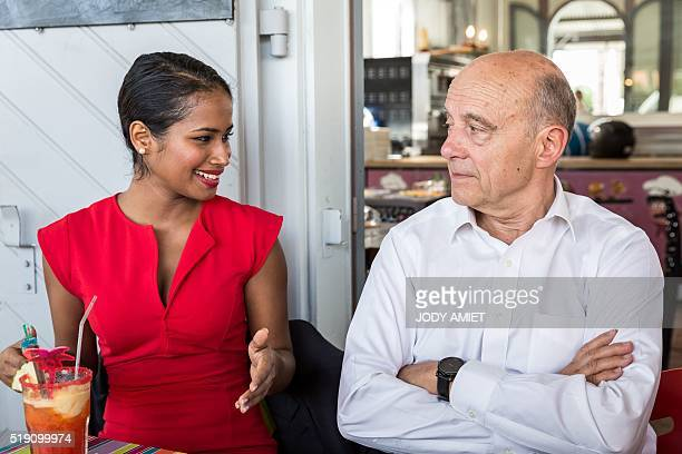 Mayor of Bordeaux and candidate for Les Republicains rightwing party primary Alain Juppe talks with a young Guianese at the cafe terrace of the Bar...