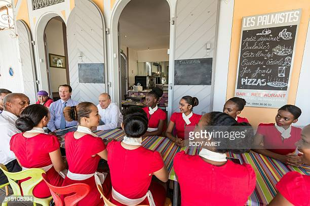 Mayor of Bordeaux and candidate for Les Republicains rightwing party primary Alain Juppe speaks with Guianese youth at the cafe terrace of the Bar...