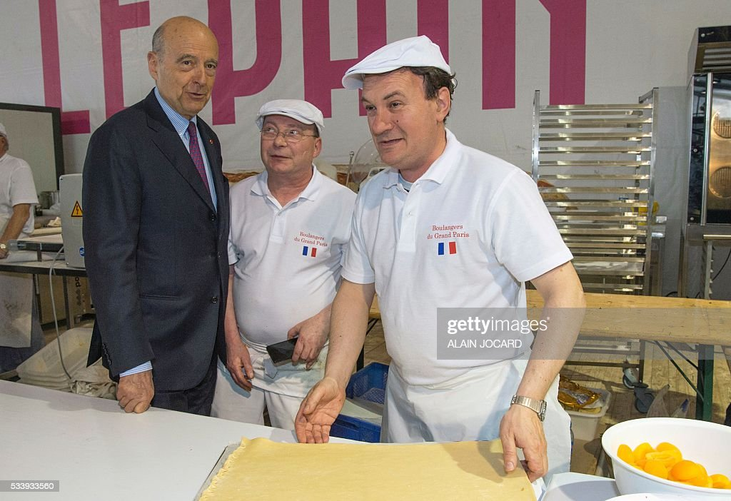Mayor of Bordeaux and France's former Prime minister Alain Juppe (R), who is vying for the right-wing nomination for the 2017 French presidential polls, visits the Bread festival at the forecourt in front of Notre-Dame de Paris, in Paris on May 24, 2016. / AFP / ALAIN
