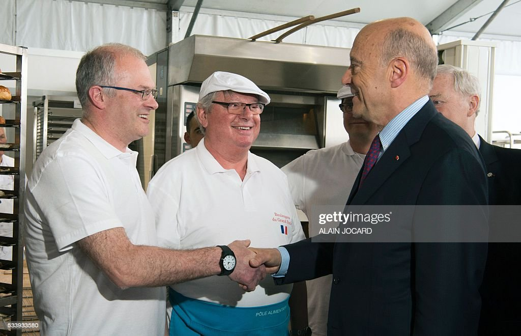 Mayor of Bordeaux and France's former Prime minister Alain Juppe (R), who is vying for the right-wing nomination for the 2017 French presidential polls, shakes hands with a baker as he arrives at the forecourt in front of Notre-Dame de Paris, in Paris on May 24, 2016 for the Bread festival. / AFP / ALAIN