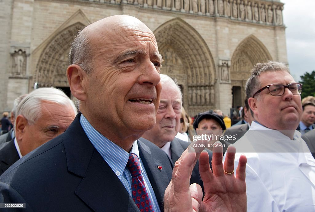 Mayor of Bordeaux and France's former Prime minister Alain Juppe (R), who is vying for the right-wing nomination for the 2017 French presidential polls, arrives to visit the Bread festival at the forecourt in front of Notre-Dame de Paris, in Paris on May 24, 2016. / AFP / ALAIN