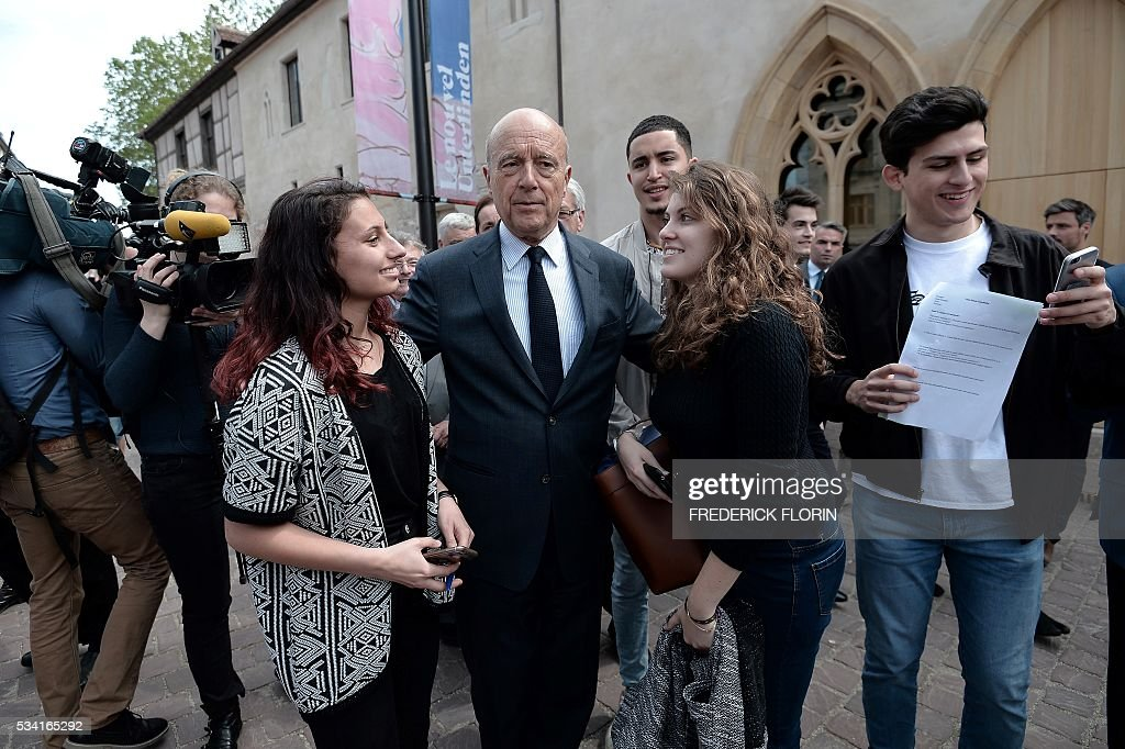 Mayor of Bordeaux and France's former Prime minister, Alain Juppe (C), who is vying for the right-wing nomination for the 2017 French presidential polls, speaks with young people after his visit of the Unterlinden Museum in Colmar, eastern France, on May 25, 2016. / AFP / FREDERICK