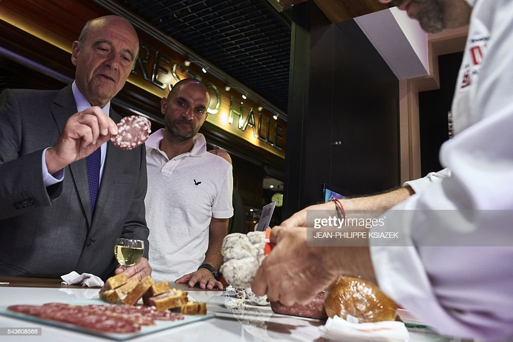 Mayor of Bordeaux and presidential candidate of the opposition Les Republicains (LR) party for the French presidential elections in 2017 Alain Juppe, holds a slice of saucisson during a visit of the Halles de Lyon Paul Bocuse, on June 29, 2016. / AFP / JEAN
