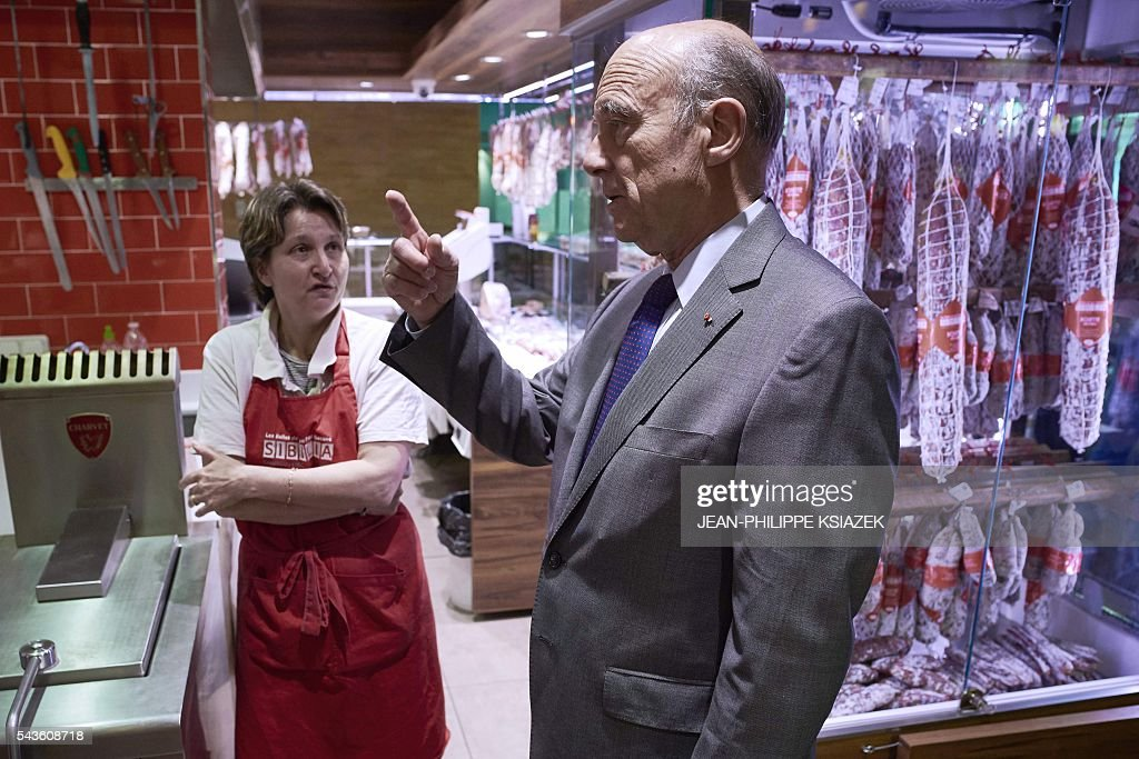 Mayor of Bordeaux and presidential candidate of the opposition Les Republicains (LR) party for the French presidential elections in 2017 Alain Juppe, gestures as he talks to a pork butcher during a visit of the Halles de Lyon Paul Bocuse, on June 29, 2016. / AFP / JEAN