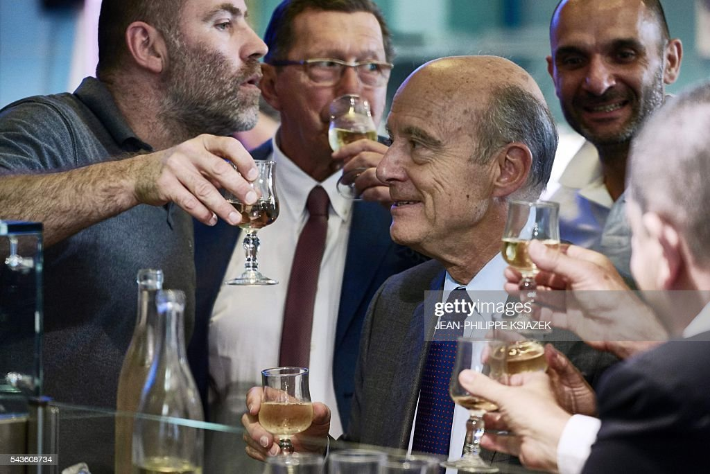 Mayor of Bordeaux and presidential candidate of the opposition Les Republicains (LR) party for the French presidential elections in 2017 Alain Juppe, reacts as he holds a glass of wine during a visit of the Halles de Lyon Paul Bocuse, on June 29, 2016. / AFP / JEAN
