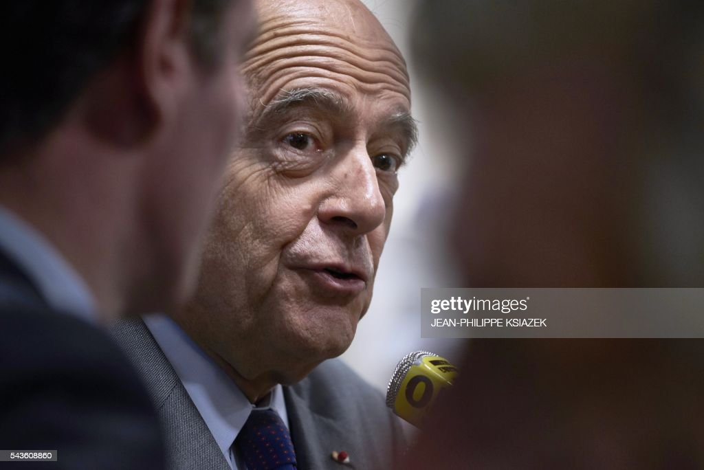 Mayor of Bordeaux and presidential candidate of the opposition Les Republicains (LR) party for the French presidential elections in 2017 Alain Juppe, answers journalists as he visits the Halles de Lyon Paul Bocuse, on June 29, 2016. / AFP / JEAN