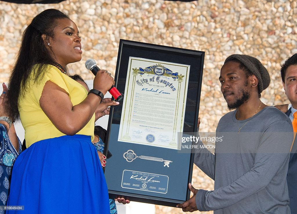 Mayor of Campton Aja Brown (L) gives the keys of the city to rapper Kendrick Lamar attends the ceremony honoring him, in Compton, California, on February 13, 2016. / AFP / VALERIE MACON