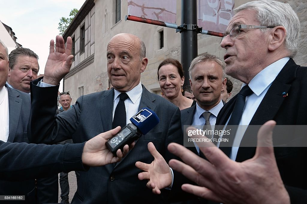 Mayor of Colmar Gilbert Meyer (R) speaks to the press as Mayor of Bordeaux and France's former Prime minister, Alain Juppe (L), who is vying for the right-wing nomination for the 2017 French presidential polls, greets people after his visit of the Unterlinden Museum in Colmar, eastern France, on May 25, 2016. / AFP / FREDERICK