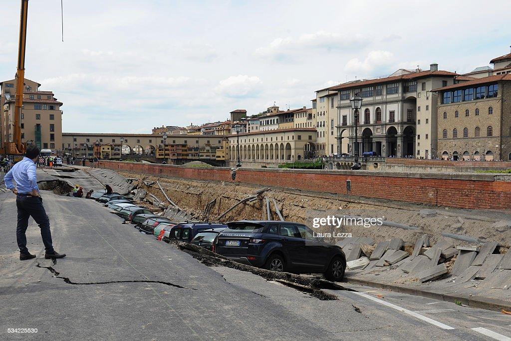 Mayor of Florence Dario Nardella assesses the damage after a road collapsed along the Arno river on May 25, 2016 in Florence, Italy. The deterioration of one or more water pipes opened a 200 m wide and 7m deep hole on Wednesday morning along the bank of the river Arno close to the famous Ponte Vecchio bridge. Many cars that were parked sunk and damages are thought to be around 5 millions euros.