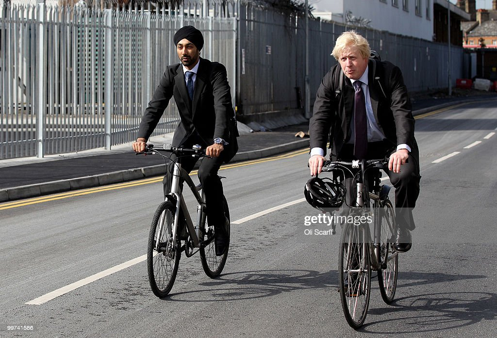 Mayor of London Boris Johnson (R) and his Advisor for Transport, Kulveer Ranger arrive on bikes to attend a press conference to announce the design for London's new Routemaster bus in Battersea Bus Depot on May 17, 2010 in London, England. The new double-decker buses, which will feature a rear open platform enabling people to 'hop-on hop-off', are claimed to be 40% more fuel efficient than current London buses and are due to go into service in 2011.