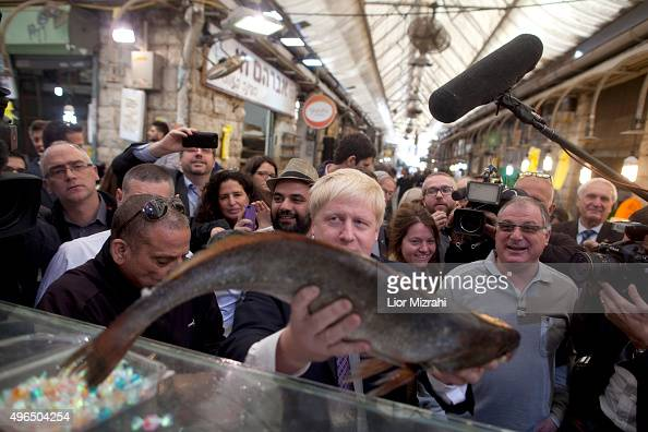 Mayor of London Boris Johnson holds a fish during a visit at the Mahane Yehuda market on November 10 2015 in Jerusalem Israel Johnson arrived in...