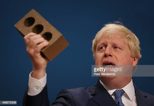 Mayor of London Boris Johnson holds a house brick aloft as he addresses the Conservative party conference on September 30 2014 in Birmingham England...