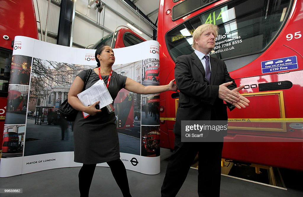 Mayor of London Boris Johnson (R) is directed by his press officer during the announcement of the design for London's new Routemaster bus, in Battersea Bus Depot on May 17, 2010 in London, England. The new double-decker buses, which will feature a rear open platform enabling people to 'hop-on hop-off', are claimed to be 40% more fuel efficient than current London buses and are due to go into service in 2011.