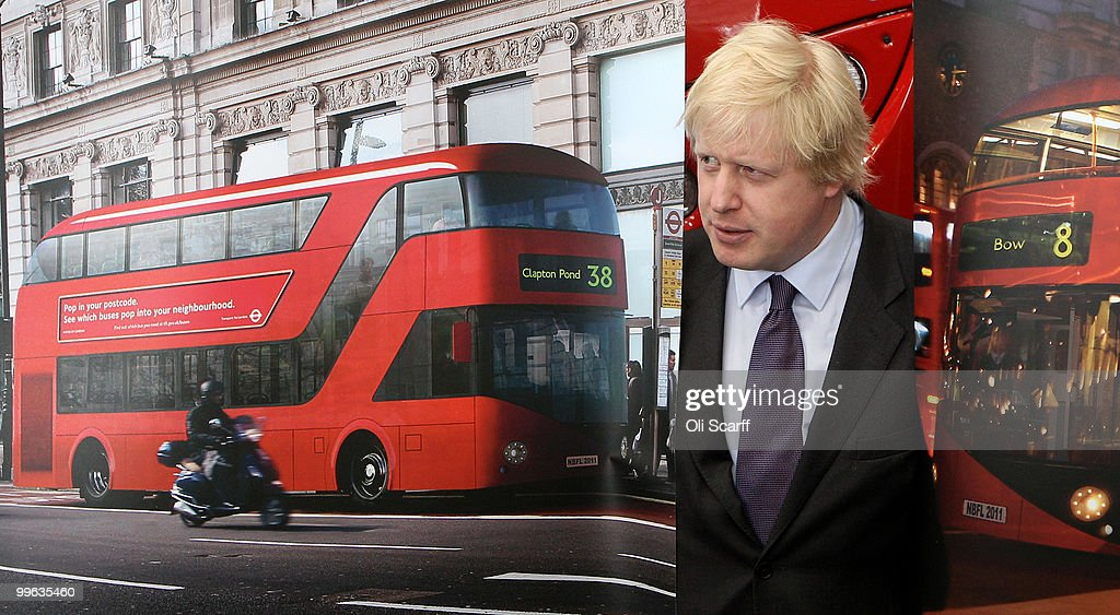 Mayor of London Boris Johnson poses with artists impressions of the design for London's new Routemaster bus on May 17, 2010 in London, England. The new double-decker buses, which will feature a rear open platform enabling people to 'hop-on hop-off', are claimed to be 40% more fuel efficient than current London buses and are due to go into service in 2011.
