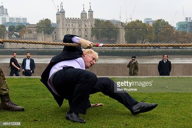 Mayor of London Boris Johnson slips over while competing in a tug of war during the launch of London Poppy Day on October 27 2015 in London England...
