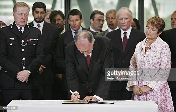 Mayor of London Ken Livingstone signs a book of condolences for the victims of the London bombings watched by Commissioner of the Metropolitan Police...