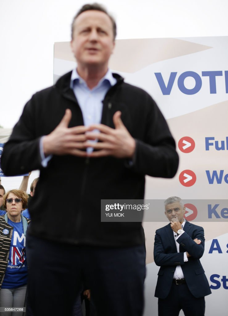 Mayor of London, Sadiq Khan, (R) listens as Britain's Prime Minister David Cameron (L) addresses supporters during the launch of the 'Britain Stronger In Europe' guarantee card in west London on May 30, 2016, ahead of the EU referendum in Britain on June 23, 2016. / AFP / POOL / Yui Mok