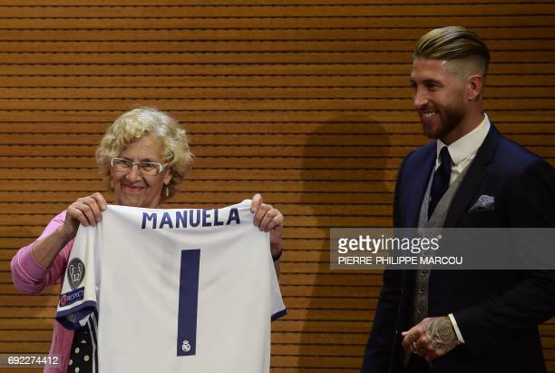 Mayor of Madrid Manuela Carmena holds up a Real Madrid team jersey with her name beside Real Madrid's defender Sergio Ramos at the Madrid Town hall...