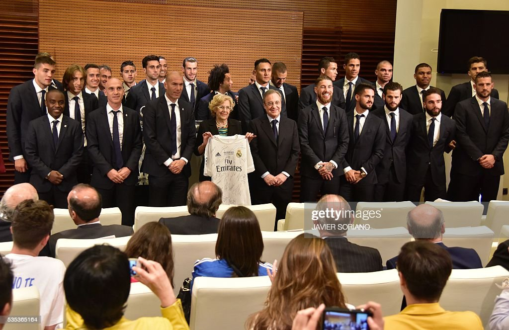 Mayor of Madrid Manuela Carmena (C L) smiles as she poses with a Real Madrid jersey sorrounded by the team in Madrid town hall on May 29, 2016 the day after winning the UEFA Champions League final foobtall match against Club Atletico de Madrid, held in Milan, Italy on May 28, 2016. / AFP / JAVIER