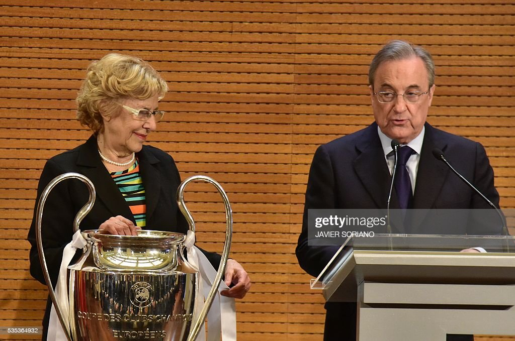 Mayor of Madrid Manuela Carmena toches the trophy in Madrid town hall on May 29, 2016 as President of Real Madrid, Florentino Perez (R) speaks the day after winning the UEFA Champions League final foobtall match against Club Atletico de Madrid, held in Milan, Italy on May 28, 2016. / AFP / JAVIER